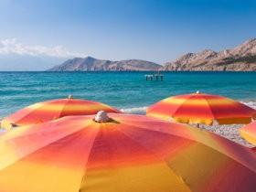 Bild: Orange Sonnenschirme am Strand bei Baska - Krk - Kroatien