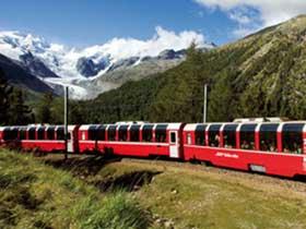 Panoramabild des Glacier Express auf grünen Hügeln vor schneebedeckten Bergen