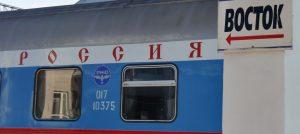 """Moskau-Wladiwostok. Transsib. Russischer Eisenbahnwagon mit kyrillischer Schrift """"Rossia"""" und Schild """"Bostok""""-Richtung Osten"""