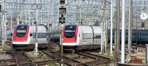 Zwei DB Züge bei Bahnhofseinfahrt mit Schienen und Bahnhofsuhr