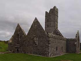 Ruine in Irland bei Regenwetter auf grüner Wiese: